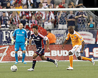 New England Revolution forward Benny Feilhaber (22) works to clear ball as Houston Dynamo midfielder Luiz Camargo (17) closes. In a Major League Soccer (MLS) match, the New England Revolution tied Houston Dynamo, 2-2, at Gillette Stadium on May 19, 2012.