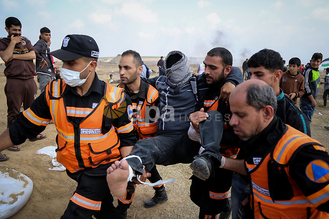 A wounded Palestinian protester is evacuated during clashes with Israeli security forces during tents protest demanding the right to return to their homeland, at the Israel-Gaza border, in Bureij in the cetner of Gaza strip on April 27, 2018. Photo by Atia Darwish