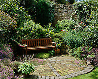 A wooden bench on a brick-inlaid patio is surrounded by greenery and flowering perennials