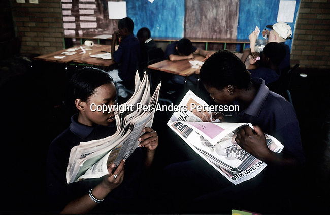 KLIPRIVER, SOUTH AFRICA APRIL 17: Phumzile Khumalo, age 16 and Rita Matlenyane, age 16, reads a newspaper in a during a class on April 17, 2003 at Sibonile (means: we have seen) School for the Blind in Klipriver, south of Johannesburg, South Africa. A blind woman founded the school in 1994. The school has about 125 students from disadvantaged communities around South Africa. Many of the children have faced rejection from their families and communities, and at Sibonile they have a chance for a good education. .(Photo: Per-Anders Pettersson)..