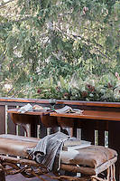 A balcony, sheltered by the branches of a fir tree, provides an outdoor space for dining and relaxation