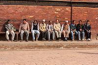 Nepal, Patan. Nepali Men Sitting by the Royal Palace.