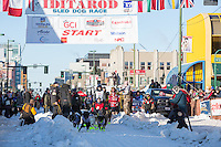 Joe Carson and team leave the ceremonial start line with an Iditarider and handler at 4th Avenue and D street in downtown Anchorage, Alaska on Saturday March 4th during the 2017 Iditarod race. Photo © 2017 by Brendan Smith/SchultzPhoto.com.