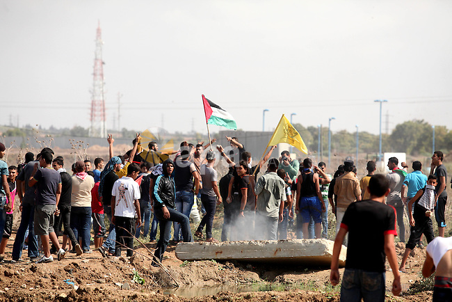Palestinian protesters gather during clashes with Israeli security forces near the Israeli border fence eastern Gaza city October 9, 2015. Israeli troops fired across the border into Gaza on Friday, killing four Palestinians and wounding at least a dozen others who were throwing stones during a rally in support of protests in Jerusalem, hospital officials in Gaza said. Photo by Ashraf Amra