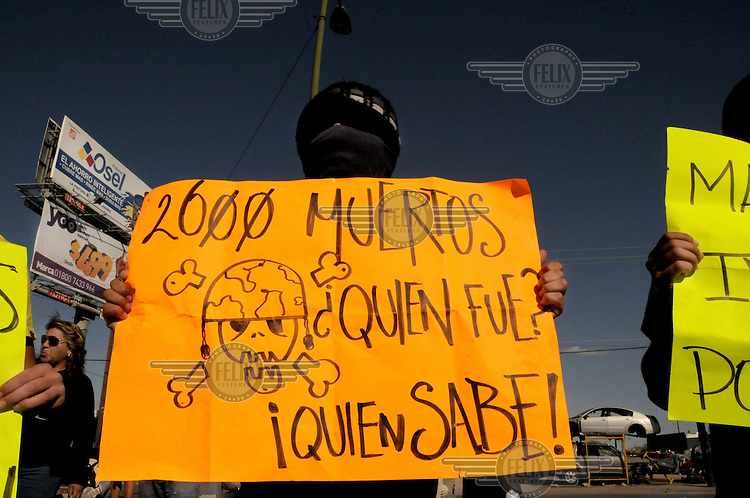 A demonstrator protests the visit of Mexican President Calderon to Cuidad Juarez. He holds a poster which reads: '2,600 dead people. Who did it? Who knows?'. Ciudad Juarez has become the world's most dangerous city. More than 2,600 people were killed in 2009. Since President Calderon declared war on the drugs cartels in 2006 and deployed thousands of troops, the violence has only increased.