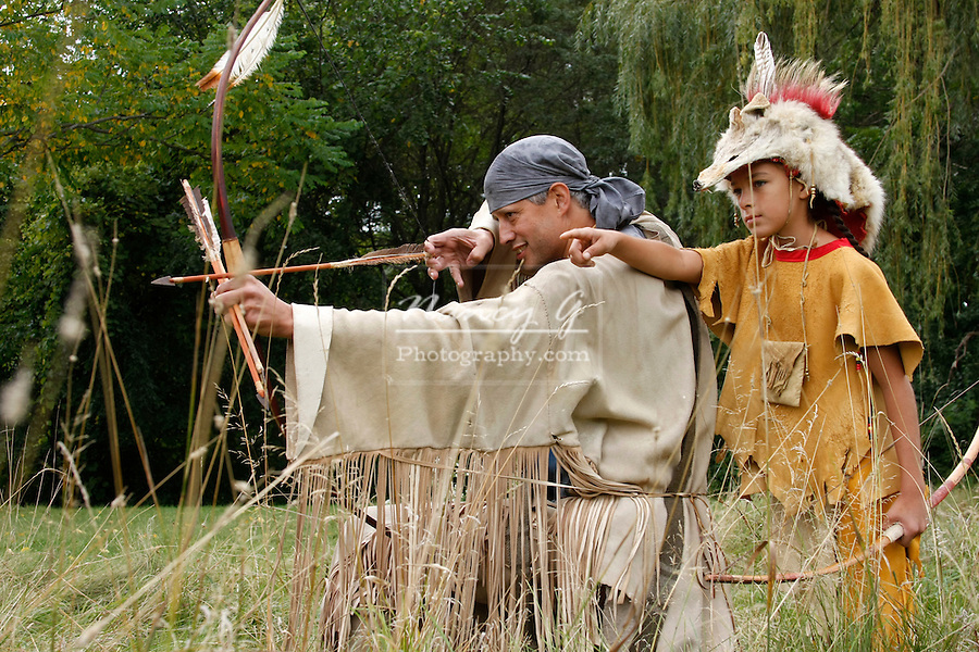 Native American Indian man with a bow and arrow hunting with a boy