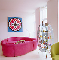 The artwork, pink modular sofa and circular glass shelf/display uni in this loft living room were all designed by Karim Rashid