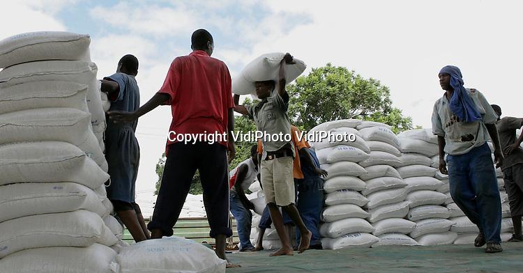 Foto: VidiPhoto..MUTARE - Zo'n 120 ingehuurde krachten lossen dagelijks de voedseltrucks van het World Food Programm (WFP) in de Oost-Zimbabwaanse stad Mutare. Trucks rijden af en aan om de hongerige bevolking van Zimbabwe te voorzien van voedsel. Het depot van Mutare is een van de grootste in het land. In totaal zijn er vier depots van het WFP. Veel Zimbabwaanse families krijgen van september tot april iedere maand maïs, bonen, rijst, olijfolie en meel van de donorlanden, waaronder Nederland. Vanaf volgende maand wordt het voedselprogramma sterk gereduceerd omdat dan het oogstseizoen in het eigen land van start gaat.