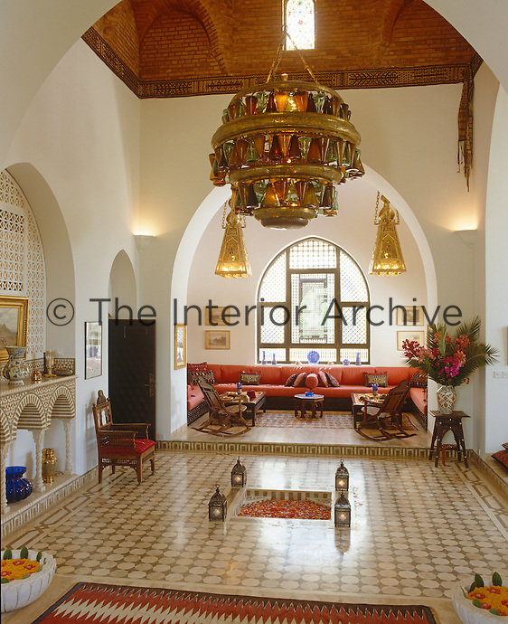A massive chandelier hangs from the high ceiling of this arched reception room with a tiled floor