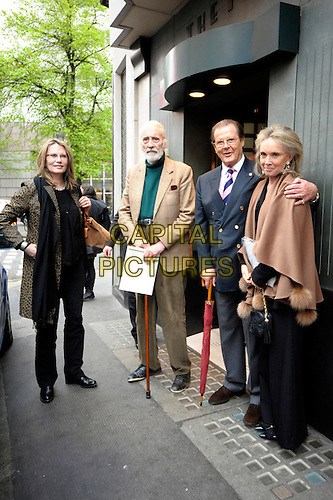 MAUD ADAMS, CHRISTOPHER LEE, SIR ROGER MOORE & KIKI (Kristina).Having a Bond reunion lunch at The Ivy Club this afternoon, London, England..April 26th, 2010.full length blue suit jacket grey gray trousers umbrella cane beige green brown black leopard print scarf wrap pashmina shawl married husband wife .CAP/DYL.©Dylan/Capital Pictures.