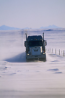 Semi truck travels through drifting and blowing snow on the James Dalton Highway (haul road) in the arctic north slope of Alaska.