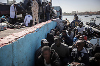 Illegal sub-Saharan migrants and refugees queue as they wait to be taken to detention centres after having been pulled from the Mediterranean Sea by the Libyan coastguard. One hundred and twenty illegal migrants and refugees were returned to the harbour of Tripoli that morning. They arrived exhausted and dehydrated and received first aid from a medical team.