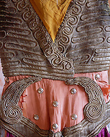 "A detail of the bodice of a costume designed for the Ballet ""Thamar"" in 1912 has swirls of embroidery appliqued onto a delicate coral backing embellished with silver studs"