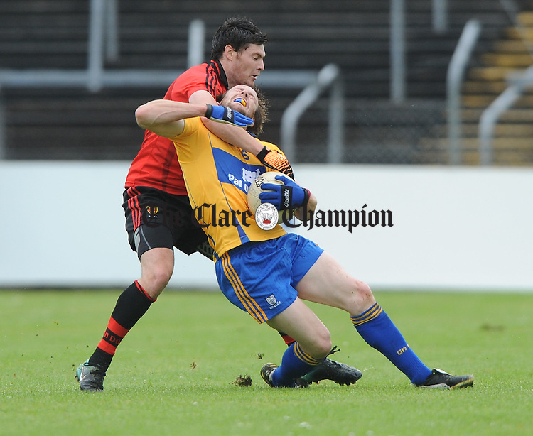 Martin Clarke of Down in action against John Hayes of Clare during their senior football championship qualifier game at Cusack Park. Photograph by John Kelly.