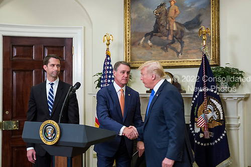 United States President Donald J. Trump shakes hands with US Senator David Perdue (Republican of Georgia), during an announcement on the introduction of the Reforming American Immigration for a Strong Economy (RAISE) Act in the Roosevelt Room at the White House in Washington, D.C., U.S., on Wednesday, August 2, 2017. The act aims to overhaul U.S. immigration by moving towards a &quot;merit-based&quot; system.  Pictured at left is US Senator Tom Cotton (Republican of Arkansas). <br /> Credit: Zach Gibson / Pool via CNP