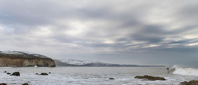 Panoramic capture of the lineup with surfer up and riding at Freshwater Bay during the Winter of 2013 with snow on the hills in the background