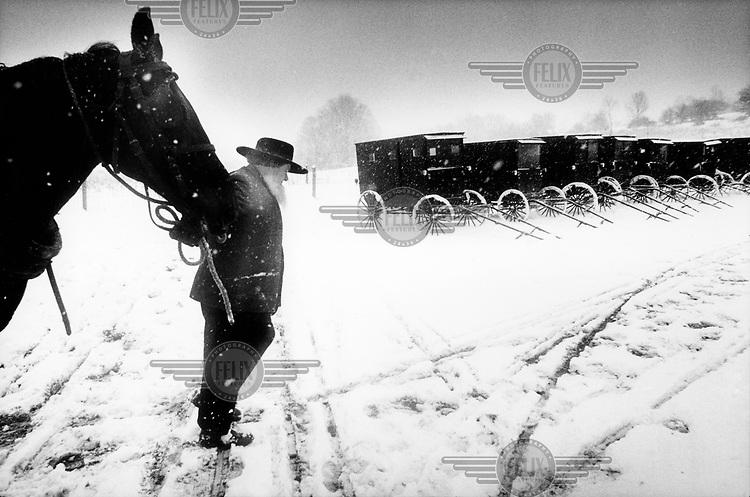 USA. Pennsylvania, .Somerset County, april 2003...De Amishgemeenschap heeft op zondag gebedsdag. Tientallen families komen per koets naar de kerk. Een man brengt zijn paard naar de stal..foto: Tim Dirven/HH...Sunday is prayerday for the Amish community. Tens of families come to church with horse and carriage..A man brings his horse to the stables..Photo: Tim Dirven/Panos Pictures.