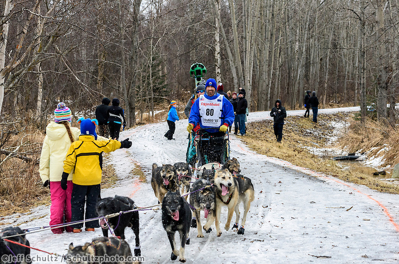 Dean Osmar<br />  and team run past spectators on the bike/ski trail with an Iditarider in the basket during the Anchorage, Alaska ceremonial start of the 2015 Iditarod race. Photo by Ed Bennett/IditarodPhotos.com