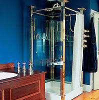 An early 20th century shower, originally installed in the Dorchester, London, was sourced at auction. The 1830s bath has a panelled mahogany surround. Salvaged floorboards and a deep cobalt blue on the walls add to the feel of a gentleman's club.