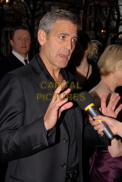 """GEORGE CLOONEY & RENEE ZELLWEGER .Attending the """"Leatherheads"""" European Film Premiere held at the Odeon cinema, Leicester Square London, England, 8th April 2008..half length black jacket  hands microphone being interviewed  funny mouth .CAP/IA.©Ian Allis/Capital Pictures"""