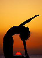 The silhouette of a woman doing a yoga back pose with an orange sun sinking into the ocean at sunset.