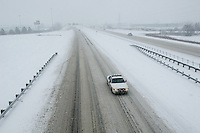 A police car patrols near empty interstate highway during a snow storm
