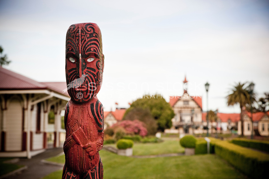 Carved traditional Maori statue at the entrance to Government Gardens with the Rotorua Museum in the background, Rotorua, North Island, New Zealand - stock photo, canvas, fine art print