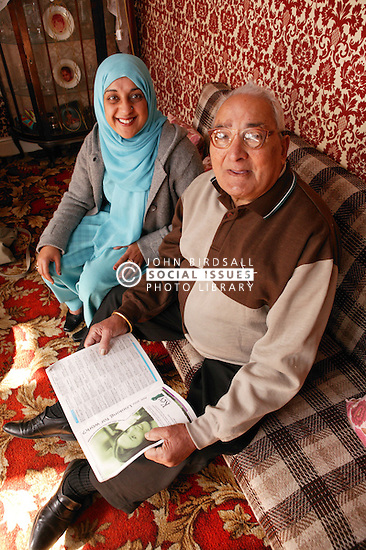 Asian carer with elderly Asian man reading at home, ***NOT TO BE USED IN THE EAST MIDLANDS***