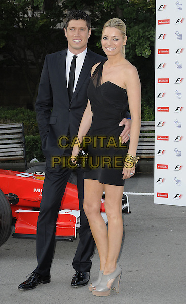 VERNON KAY & TESS DALY .The F1 Party held at the Natural History Museum, London, England, UK..5th July 2010.Formula one full length black sheer one shoulder dress clutch bag wooden wood grey gray wedges platform suit tie white shirt married husband wife peep toe arm around waist.CAP/CAN.©Can Nguyen/Capital Pictures.