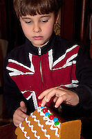 Boy age 7 wearing a UK Union Jack flag shirt decorating a Christmas gingerbread house. St Paul Minnesota USA
