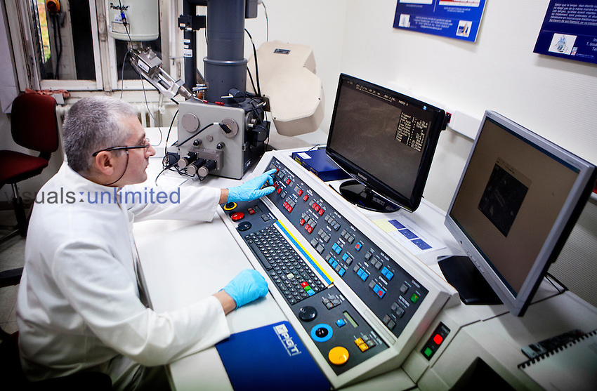 Scientist using a Scanning Electron Microscope (SEM), French National Police, Criminal Research Institute, Rosny-sous-Bois, France.