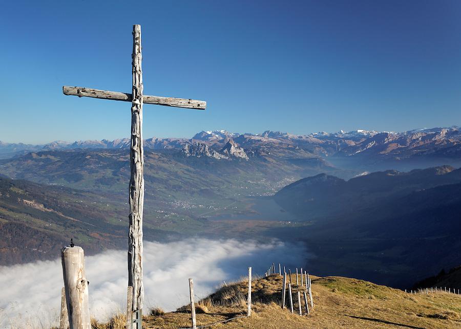 Wooden cross near summit of Mount Rigi overlooking Lauerzersee and town of Schwyz, Switzerland, Europe