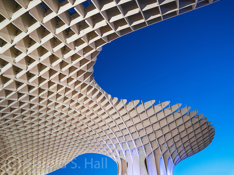 Metropol Parasol is a giant wooden structure located in a major plaza in the old section of Seville, Spain.  It was designed by the German architect Jürgen Mayer and consists of six parasols providing much needed shade.  The locals refer to it as the mushroom due to its appearance from some angles.  It is the worlds largest wooden structure, made of imported elm from Finland.  The reason for the intense blue sky is because the photo was taken after sunset, during what photographers call the 'blue hour.'