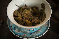 Green tea leaves in Chinese cup, Puer-tea shop, Jinghong, Yunnan, China. 11 November 2012.