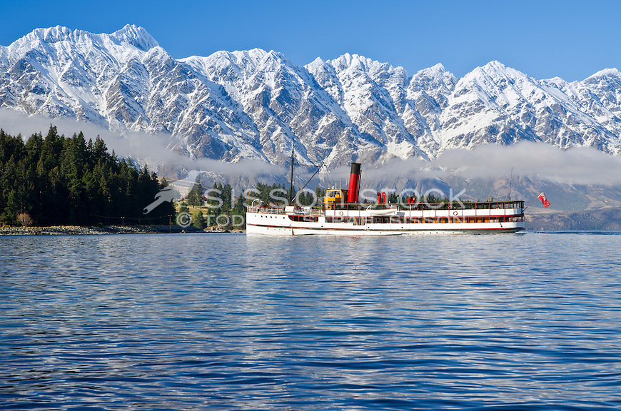 The Earnslaw steamer ship cruises past The Remarkables mountains on winter boat trip, Queenstown