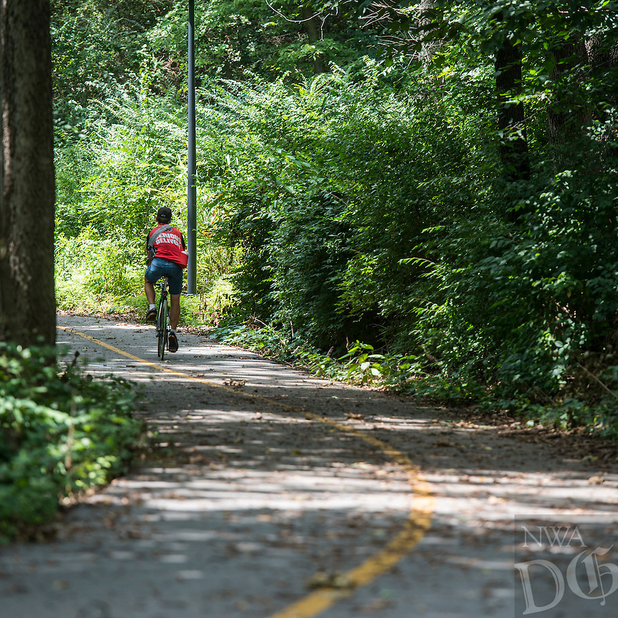 STAFF PHOTO ANTHONY REYES &bull; @NWATONYR<br /> A cyclist pedals along A section of the Oak Ridge Trail Monday, Aug. 11, 2014 near Center Street in Fayetteville.