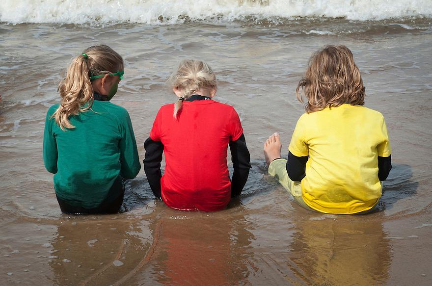 Nederland, Zandvoort, 15 aug 2014<br /> Meisjes zitten in de branding aan het strand.<br /> Foto (c) Michiel Wijnbergh