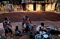 Two women with their children sit beside drying cocoa seeds at the Georgekro cocoa farmers' camp.