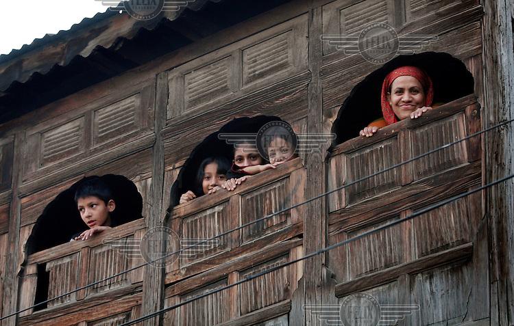 Family looking out from their house during a curfew in Srinagar, Kashmir,India. © Fredrik Naumann/Felix Features