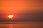 Windansea, La Jolla, California; a large orange sun sets over the Eastern Pacific Ocean