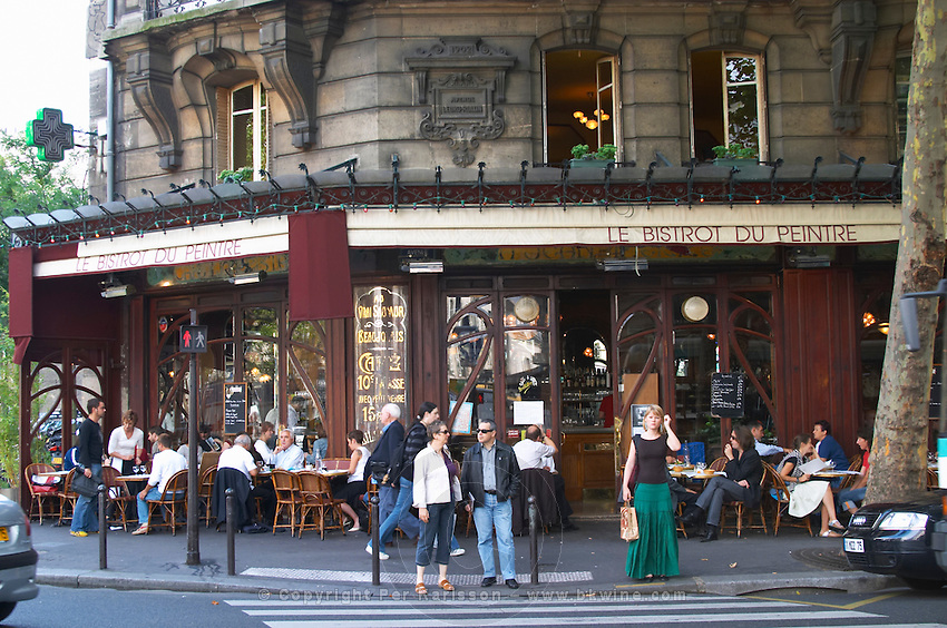 Le Bistrot du Peintre cafe bar terrasse terasse outside seating on the sidewalk. People sitting in chairs at tables eating and drinking outside at lunch time. People standing in front of a pedestrian crossing waiting for traffic The Bistrot du Peintre is an old fashioned Paris café cafe bar restaurant of art nouveau design with polished brass, mirrors and old signs