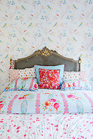 Layers of colourful, floral fabrics are a feature of one of the bedrooms. The antique bed adds to the romantic feel of the room, surrounded by wallpaper peppered with birds