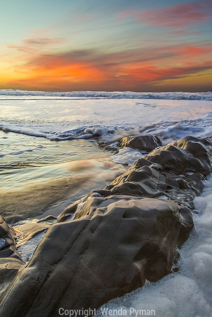 The fading sunset lights up the incoming surf and rocks at Baker Beach.