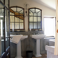 A view through an open part-glazed door leads to a part panelled bathroom. Two paned mirrors hang above two his and hers pedestal washbasins.