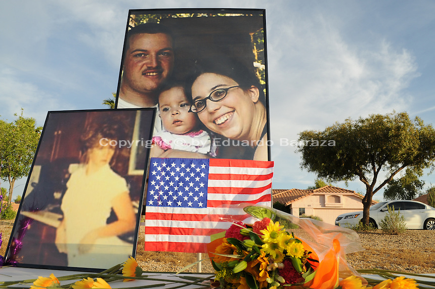 """Gilbert, Arizona – Friends and family of the Mederos Family gathered to hold a memorial for the four victims of the Gilbert Massacre occurred on May 2, 2012. According to Gilbert Police, Lisa Mederos, Amber Mederos, baby Lilly Mederos, and Jim Hiott (Amber's fiancé) were all killed by notorious white supremacist and Neo-Nazi Jason """"J.T."""" Ready before taking his own life. In this image, enlarged photographs of the four victims of the Gilbert massacre rise above a table with flowers at the memorial service. Photo by Eduardo Barraza © 2012"""