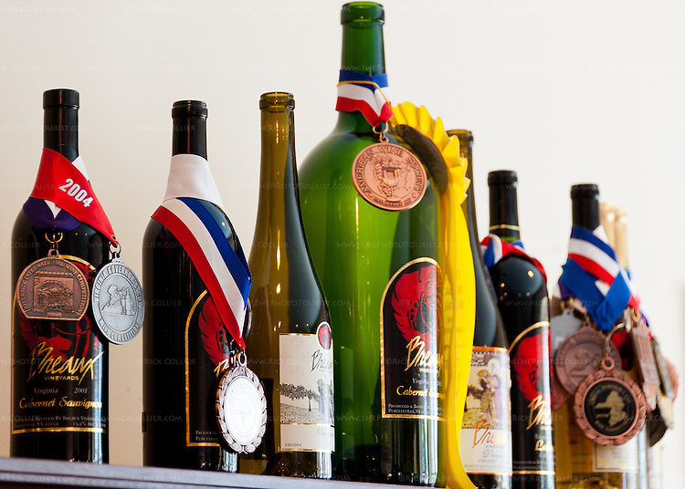 Empty wine bottles display their medals and ribbons, on a shelf in the tasting room at Breaux Vineyards.