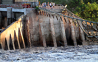 Onlookers stand at the edge of the breached dam at Lake Delhi early Sunday morning, July 25, 2010.  Flood water breached and destroyed the dam the day before, emptying the nine mile long lake.