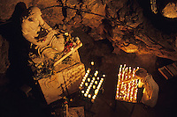 Woman burning candle at Troglodyte Sainte-Marie Madeleine Holy Cave, France, Provence, Sainte-Baume Mountain