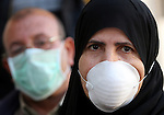 Palestinians wear face masks on a street in Gaza city for fears of A/H1N1 virus in Gaza city on Dec 13, 2009. The virus killed a sixth Palestinian victim since it was discovered in the Gaza Strip on Sunday. photo by Wissam Nassar