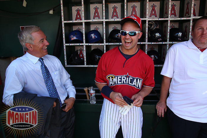 ANAHEIM - JULY 13:  Nick Swisher of the American League laughs with Bobby Valentine in the dugout before the All Star Game at Angel Stadium on June 13, 2010 in Anaheim, California. Photo by Brad Mangin